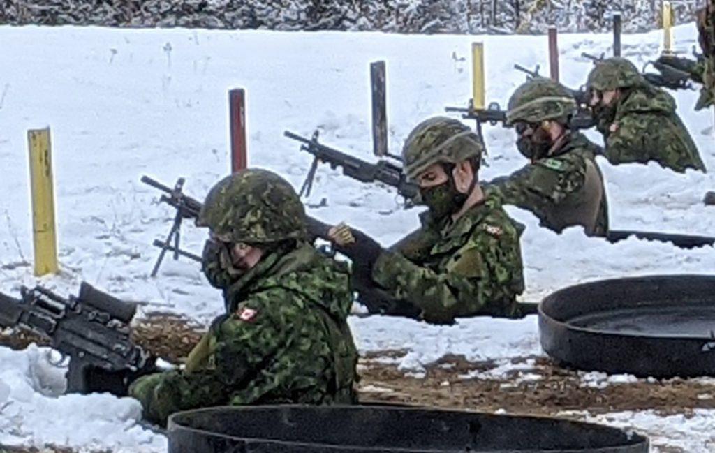 Canadian soldiers firing machine guns